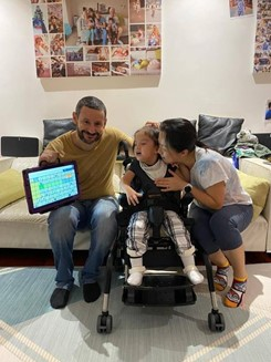 Man with mother and her daughter in a wheelchair with a communication device