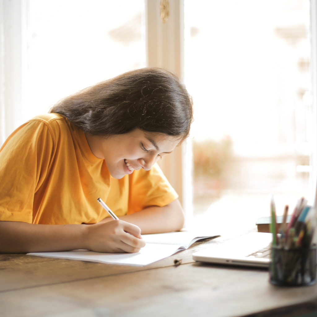 Girl in yellow top at desk writing next to a laptop