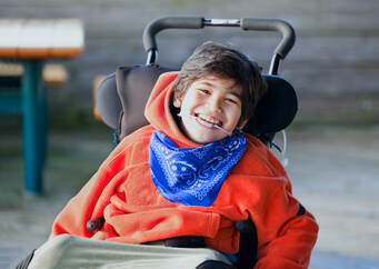 Image of child smiling in wheelchair with red top