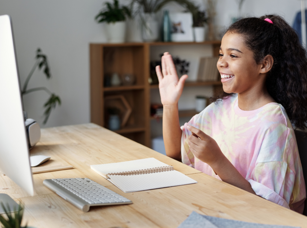 Child smiling looking at a computer screen, raising her hand at her desk